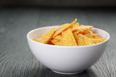 Tortilla chips in white bowl on wooden table Stock Photo