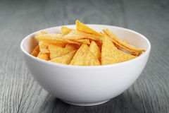 Tortilla chips in white bowl on wooden table Stock Photos