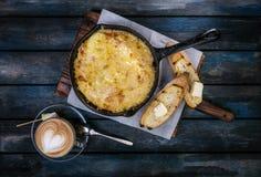 Tortilla clásica del desayuno en un sartén en un soporte de madera con la tostada y el café Fondo de madera coloreado Visión supe Foto de archivo libre de regalías
