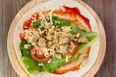 Tortilla con el pollo, tomates, ensalada Fotos de archivo