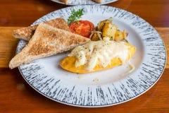 Tortilla con la patata, tomates perejil y queso feta y pan en la placa blanca en la tabla de madera Fotografía de archivo