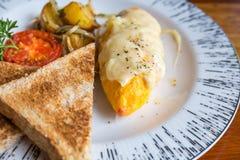 Tortilla con la patata, tomates perejil y queso feta y pan en la placa blanca en la tabla de madera Imágenes de archivo libres de regalías