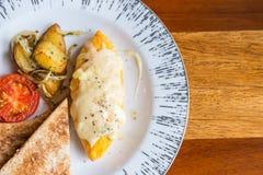 Tortilla con la patata, tomates perejil y queso feta y pan en la placa blanca en la tabla de madera Fotos de archivo