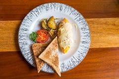 Tortilla con la patata, tomates perejil y queso feta y pan en la placa blanca en la tabla de madera Fotos de archivo libres de regalías