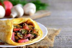 Tortilla con las setas y los tomates La tortilla hecha en casa con las setas fritas, los tomates frescos y el eneldo se pone verd Fotografía de archivo libre de regalías