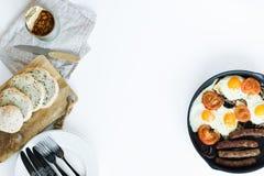 Tortilla con los tomates en una cacerola en un fondo blanco foto de archivo libre de regalías