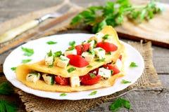 Tortilla con queso, los tomates y el perejil en una placa en viejo fondo de madera Plato relleno de la tortilla Estilo de la vend Imagenes de archivo