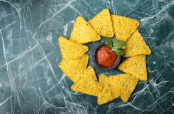 Tortilla Corn Chips or Nachos with sauce in a black bowl, on a beautiful, blue background. View from above. stock photography