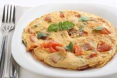 Tortilla de huevos con el tomate y el jamón Foto de archivo libre de regalías