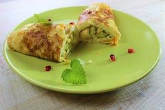 Tortilla del huevo frito del desayuno de la mañana rellena con el calabacín en la placa verde Cortarlo con un cuchillo y una bifu imágenes de archivo libres de regalías