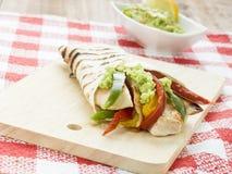 Tortilla deliciosa del abrigo con guacamole picante de las verduras del pollo Foto de archivo