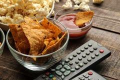 Tortilla en popcorn, TV ver op een bruine houten achtergrond concept thuis het letten van op films Close-up royalty-vrije stock afbeeldingen