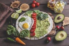 Tortilla met guacamoleavocado, gebraden ei en tomaat, spinaziebladeren Vegetarische schotel stock fotografie