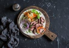 Tortilla met rundvleeslapje vlees, gemarineerde wortelen en kool Heerlijke lunchsnack Op een donkere achtergrond stock afbeeldingen