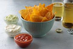 Tortilla mexicaine de casse-croûte dans la cuvette bleue avec des sauces et la bière à immersion sur la table images stock