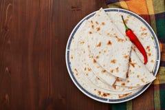 Tortilla mexicana del flatbread en placa en la tabla de madera foto de archivo