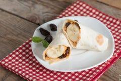 Tortilla opakunek z masłem orzechowym, rodzynką i bananem na whi, fotografia royalty free