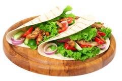 Tortilla opakunek z pieczonych kurczaków warzywami na drewnianej desce odizolowywającej na białym tle i mięsem zdjęcia stock