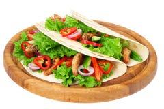 Tortilla opakunek z pieczonych kurczaków warzywami na drewnianej desce odizolowywającej na białym tle i mięsem zdjęcie royalty free
