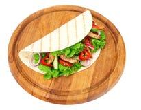Tortilla opakunek z pieczonych kurczaków warzywami na drewnianej desce odizolowywającej na białym tle i mięsem fotografia stock