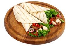 Tortilla opakunek z pieczonych kurczaków warzywami na drewnianej desce odizolowywającej na białym tle i mięsem obrazy royalty free