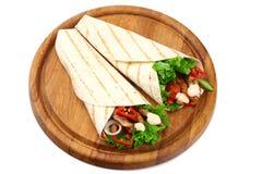 Tortilla opakunek z pieczonych kurczaków warzywami na drewnianej desce odizolowywającej na białym tle i mięsem obraz stock