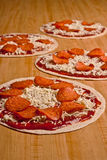 Tortilla Pizzas Four. Four uncooked pepperoni and cheese tortilla pizzas on a long wooden surface Stock Images