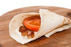 Tortilla rellena con la carne del pollo, la salsa de tártaro y el tomate Imágenes de archivo libres de regalías