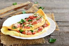 Tortilla rellena con las salchichas fritas, el queso rallado y el perejil en una placa, la bifurcación, el cuchillo y una tabla d Fotografía de archivo