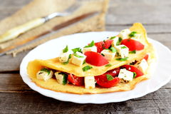 Tortilla rellena con queso, los tomates frescos y el perejil Tortilla rellena en una placa y en viejo fondo de madera Eggs receta Foto de archivo
