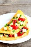 Tortilla rellena con queso, los tomates frescos y el perejil Tortilla rellena en una placa y en viejo fondo de madera Eggs receta Imagen de archivo libre de regalías