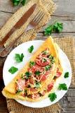 Tortilla rellena deliciosa en una placa Tortilla rellena con las salchichas fritas, el queso rallado y el perejil, bifurcación, c Foto de archivo
