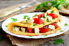 Tortilla rellena hogar en una placa Egg la tortilla rellena con los tomates, el queso y el perejil verde imagenes de archivo