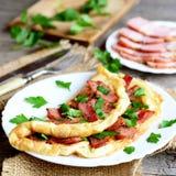 Tortilla sabrosa del tocino Tortilla frita rellena con tocino y perejil para las rebanadas del tocino del desayuno en una placa,  foto de archivo libre de regalías