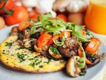 Tortilla sana del desayuno con el tomate y las setas Fotos de archivo