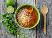 Tortilla Soup. With Cheese, Lime, Cilantro and Wooden Spoon on Rustic Wood Background Stock Photography