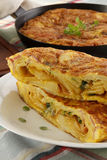 Tortilla - spanish omelete. On wood table, pan on back, soft focus royalty free stock images