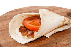 Tortilla stuffed with chicken meat, tartar sauce and tomato Royalty Free Stock Images
