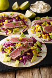 Tortilla with tuna steak, sesame and fresh vegetables close-up. royalty free stock photo
