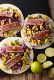 Tortilla with tuna steak, sesame and fresh vegetables close-up. stock photo