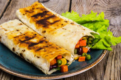 Tortilla with vegetable mix on blue plate stock photography