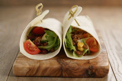 Tortilla wrap sandwiches with beef and vegetables on olive board Stock Image