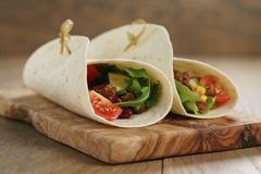 Tortilla wrap sandwiches with beef and vegetables on olive board Royalty Free Stock Photos