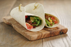 Tortilla wrap sandwiches with beef and vegetables on olive board Royalty Free Stock Images