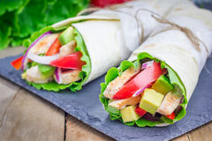Tortilla wraps with roasted chicken, avocado, tomato, onion and puprika stock images
