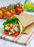Tortilla wraps with roasted chicken fillet, fresh vegetables and sauce. In paper bag Royalty Free Stock Photography