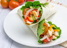 Tortilla wraps with roasted chicken fillet, fresh vegetables and sauce. On white plate Stock Photo