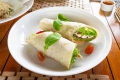 Tortillaomslag met kippenvlees en groenten bij het traditionele schotel toping met spinazie stock foto