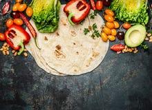 Tortillas flach und verschiedenes Gemüse für die Tacos oder Burrito, die auf rustikalem Hintergrund, Draufsicht machen Stockfotografie