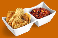 Tortillas and salsa. Fiesta: Tortillas chips and salsa in white serving dish on fun orange background Royalty Free Stock Photo